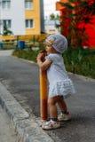 Muchacha adorable que se divierte el día de verano una niña se coloca en la trayectoria de la transición y se aferra en la cerca, fotografía de archivo