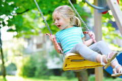 Muchacha adorable que se divierte en un oscilación el día de verano Fotografía de archivo