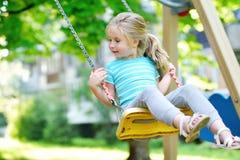 Muchacha adorable que se divierte en un oscilación el día de verano Imagenes de archivo