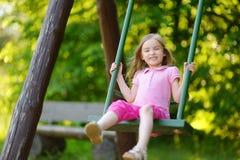 Muchacha adorable que se divierte en un oscilación Fotografía de archivo libre de regalías