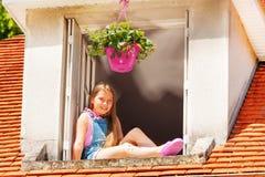 Muchacha adorable que se sienta en la repisa de la ventana del ático fotos de archivo