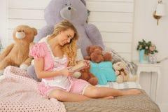 Muchacha adulta bonita con su diario secreto en su dormitorio blanco con muchos osos de peluche de la felpa imagen de archivo libre de regalías