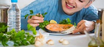 Muchacha adulta feliz que adorna pescados fritos con las hierbas Foto de archivo libre de regalías