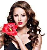 Muchacha adulta hermosa con los labios y la flor rojos brillantes cerca del fa Foto de archivo libre de regalías
