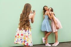 Muchacha adulta joven hermosa tres que toma la foto con un teléfono elegante Fotografía de archivo libre de regalías