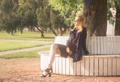 Muchacha adulta joven que sienta al aire libre luz del sol Fotografía de archivo