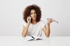 Muchacha africana aburrida que habla en el teléfono que se sienta en la tabla sobre el fondo blanco Copie el espacio Imagen de archivo