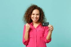 Muchacha africana alegre en la ropa casual que hace la tarjeta de banco de crédito del control del gesto del ganador aislada en l imagen de archivo