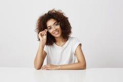 Muchacha africana atractiva joven del diseñador de moda en vidrios que sonríe mirando la cámara que se sienta en la tabla sobre b Fotografía de archivo