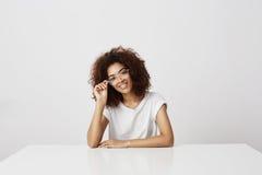 Muchacha africana atractiva joven en vidrios que sonríe mirando la cámara que se sienta en la tabla sobre la pared blanca Moda fu Imágenes de archivo libres de regalías