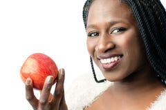 Muchacha africana atractiva que sostiene la manzana roja Imágenes de archivo libres de regalías