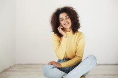 Muchacha africana blanda hermosa que sonríe con los ojos cerrados que escuchan la música en el goce de los auriculares Imagen de archivo