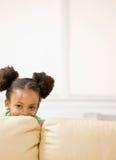 Muchacha africana dañosa que oculta detrás del sofá Imagenes de archivo