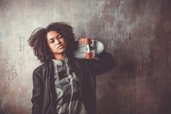 Muchacha africana del adolescente con el monopatín delante de un muro de cemento Fotografía de archivo