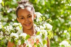 Muchacha africana del adolescente con las flores en el peral Fotos de archivo