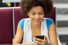 Muchacha africana del estudiante con smartphone en conferencia fotografía de archivo libre de regalías