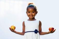Muchacha africana dulce que sostiene la manzana en cada mano Fotografía de archivo libre de regalías