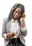 Muchacha africana encantadora alegre que sostiene el teléfono móvil y el listeni Imagenes de archivo