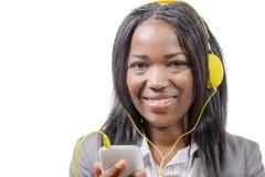 Muchacha africana encantadora alegre que sostiene el teléfono móvil y el listeni Imágenes de archivo libres de regalías