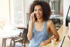 Muchacha africana hermosa alegre feliz que sonríe mirando la cámara que habla en el teléfono que se sienta en café Fotos de archivo libres de regalías