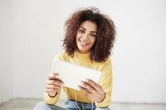 Muchacha africana hermosa en auriculares que sonríe mirando la tableta de la tenencia de la cámara que se sienta en piso sobre el Fotografía de archivo libre de regalías