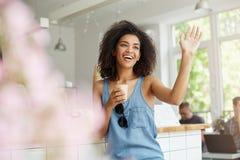 Muchacha africana hermosa feliz que se sienta en café de consumición de risa sonriente del saludo del café Imágenes de archivo libres de regalías