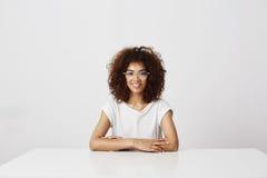 Muchacha africana hermosa joven en vidrios que sonríe mirando la cámara que se sienta sobre el fondo blanco Imagen de archivo