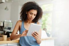 Muchacha africana hermosa joven que mira la relajación de reclinación que se sienta de la pantalla de la tableta el café Imagen de archivo libre de regalías