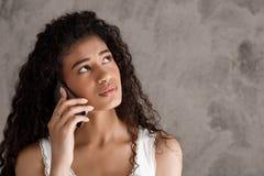 Muchacha africana hermosa que habla en el teléfono sobre fondo beige Foto de archivo