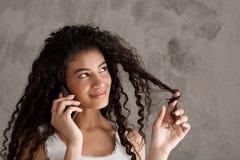 Muchacha africana hermosa que sonríe, hablando en el teléfono sobre fondo beige Fotos de archivo libres de regalías