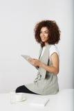 Muchacha africana hermosa que sonríe sosteniendo la tableta que se sienta en el lugar de trabajo Copie el espacio Imagenes de archivo