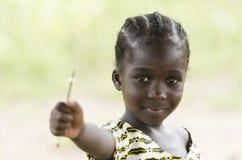 Muchacha africana hermosa que sostiene una pluma al aire libre Imagenes de archivo