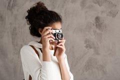 Muchacha africana hermosa que toma imágenes con la cámara sobre fondo beige Imagen de archivo libre de regalías