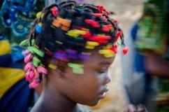 Muchacha africana joven con el baile maravillosamente adornado del pelo, muy colorido con la falta de definición de movimiento pr Imágenes de archivo libres de regalías