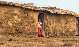Muchacha africana joven de la tribu del masai en la entrada de su hogar Imagen de archivo libre de regalías