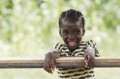 Muchacha africana joven de risa que se sienta en su escritorio Foto de archivo