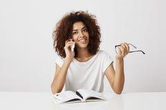 Muchacha africana joven elegante que toma una rotura de su estudio, hablando con la madre en el teléfono, discutiendo el nuevo no Fotografía de archivo libre de regalías