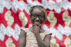 Muchacha africana joven hermosa con los accesorios tradicionales en pelo que sonríe en la cámara Fotografía de archivo