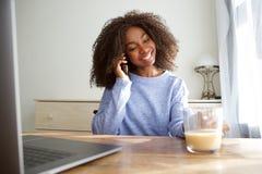 Muchacha africana joven hermosa que se sienta en la tabla por mañana y que habla en el teléfono móvil Fotos de archivo