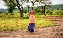 Muchacha africana joven que presenta en un pueblo de la tribu del Masai Fotos de archivo