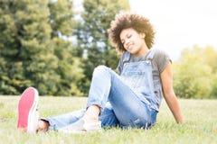 Muchacha africana joven que se relaja en parque Imágenes de archivo libres de regalías