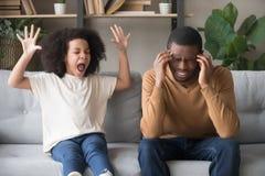 Muchacha africana obstinada del niño en rabieta que grita en el padre negro imagenes de archivo