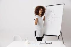 Muchacha africana que coloca whiteboard cercano del marcador en el lugar de trabajo Imagen de archivo