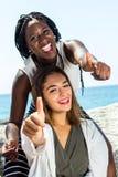 Muchacha africana que hace los pulgares para arriba con el amigo caucásico Fotos de archivo libres de regalías