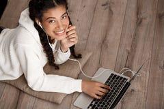 Muchacha africana que mecanografía en el ordenador portátil, sonrisa, mintiendo en piso de madera Foto de archivo libre de regalías