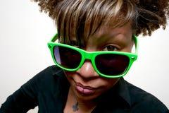 Muchacha africana que mira fijamente sobre los vidrios verdes Imagen de archivo