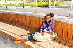 Muchacha africana que sienta y que sostiene el monopatín Imágenes de archivo libres de regalías
