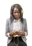 Muchacha africana que sostiene el teléfono móvil y que escucha la música Imágenes de archivo libres de regalías