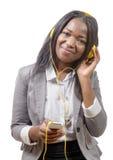 Muchacha africana que sostiene el teléfono móvil y que escucha la música Imagen de archivo