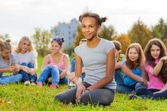Muchacha africana y amigos que se sientan en prado verde Foto de archivo